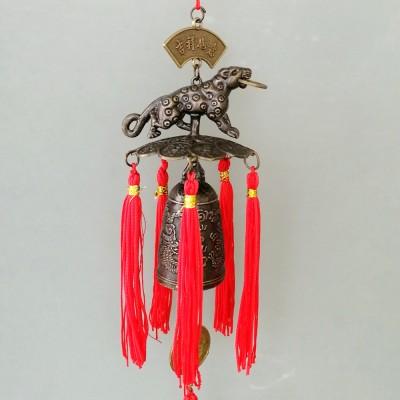 Колокольчик с тигром, держащим в зубах монетку, украшенный красными кистями.